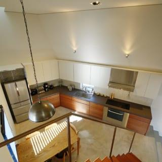 3階へと至る階段から見たダイニング。斜めの壁と折り返し部分に、キッチンがキレイに収まる