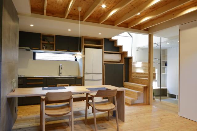 1階のダイニング。階段上部の窓からは、明るい光が差し込む。テーブル横のセメントボードの壁は、グレーでまとめた階段手すりのアイアンやキッチンと統一感がありつつも、独特の素材感で趣を添える。写真右の白い引き戸の取っ手は、高級感あふれるウォルナット