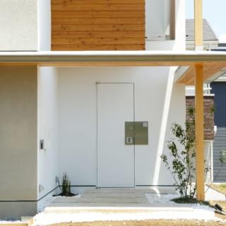 玄関ドアは周囲の吹き付け仕上げの外壁と同じ素材。手触りを考慮し、ドアノブ付近だけステンレスを貼っている。外観全体のデザインを損ねない、さりげない存在感
