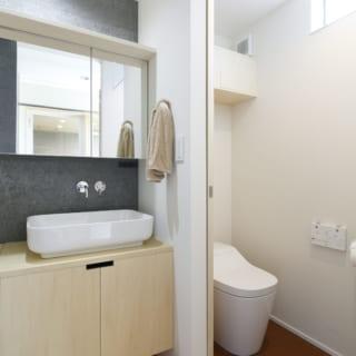 1階の洗面室とトイレは隣接し、トイレ用手洗いが不要な造り。トイレ上部から入る光が洗面室も明るく照らす
