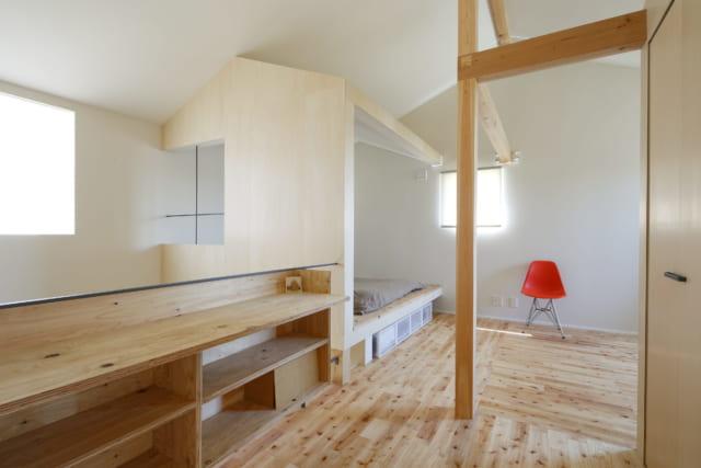 2階廊下から寝室側を見る。廊下は吹抜けに面し、大きな窓からたっぷり入る光が2階全体に行きわたる。写真左奥は寝室。ここも、三角屋根の「おうち」をモチーフにしたデザイン。椅子が置かれた空間は、将来仕切ることもできる第2のリビング