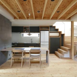 1階LDK。リビングからキッチン・ダイニングを見る。木を多用した空間だが重さはなく、ルイスポールセンのペンダントライトやマルニ木工の椅子といった名作家具と好相性。天井の一部はボードを張らない現し(あらわし)仕上げで高さと表情を出し、広がりのある印象に