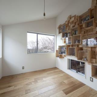中二階の書斎は2面採光で明るさを確保しながら、景色も楽しめるつくり。壁にはオリジナルの飾り棚が設けられ、S様のコレクション置き場に