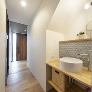 玄関からパントリー、キッチンへと続くアプローチは回遊性も抜群。階段下のスペースには手洗い場も