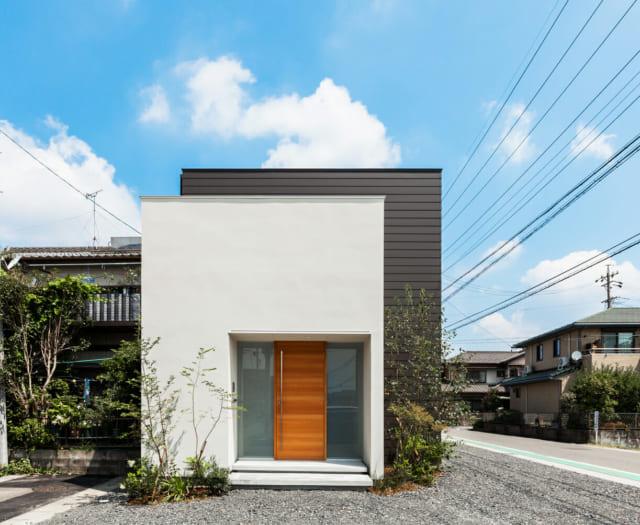 玄関側真正面からの外観。左手に細い道路がある。白と黒のキューブを合わせたような、コンパクトでシンプルなデザイン
