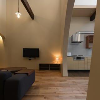 生活空間のキッチンも壁を利用し見えにくくした。キッチンは以前のものを再利用。扉パネルを変え印象を一新