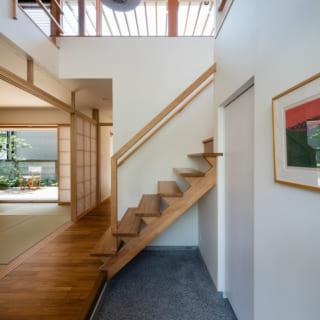 1階の玄関内部。正面の階段まわりは吹抜けになっており、2階のデッキを通したやさしい自然光が入る