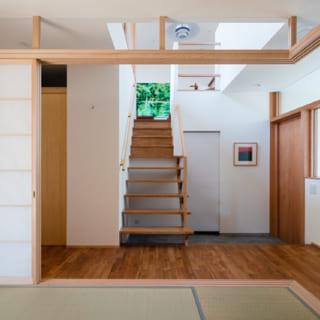 1階の和室から玄関土間を見る。和室は、障子を引き寄せて空間を開放できるようになっており、玄関ホールを広く感じられる。玄関を入るとこの和室を通して庭も見え、より広々とした印象に。プライベート空間を通らずに来客を案内できるというメリットもある