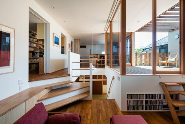 写真手前のスペースが2階のリビング。2階はスキップフロアのため、リビングは奥のダイニングより一段低い。その分、リビングは天井の高いゆとりある空間に。写真右のガラス越しに広がるデッキの窓枠は木製なのでインテリアとの馴染みが良く、内と外のつながりも良い