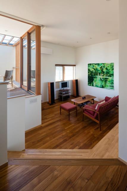 2階通路からリビングを見る。リビングは天井が3.2m。大きな絵画が映える、ホテルロビーのような空間