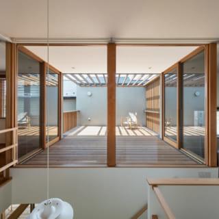 室内から見た2階のデッキ。住空間に入り込んだ造りになっており、さらに、木製の窓枠は木柱があるだけのようにも見え、内と外の境界があいまいになる不思議な開放感をもたらす。デッキの手前には吹抜けの階段があり、デッキから入る光は1階にも届く