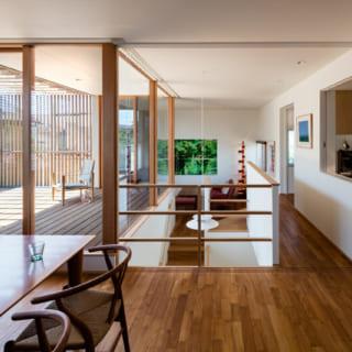 2階のキッチンからダイニング・リビングを見る。キッチンに立つと、絵を飾るためにつくった西の壁がちょうど正面に見えるレイアウト。家事をする奥さまが日常的に絵画鑑賞を楽しめる。ダイニングスペースはガラス扉で仕切ることもでき、冷暖房を効率的に使える