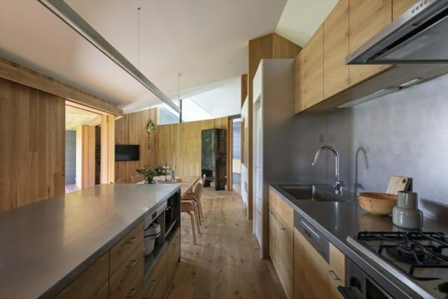 キッチンはバイブレーション加工を施したステンレスを使用し、男性的なイメージに仕上げた。キッチン裏側のパントリーには、左右どちらからでもアクセスできる。写真上部の吊り照明は雰囲気に合わせ造作。4.5mの長さがあり、「この空間スケールだからできること」と洋光さん
