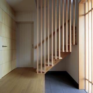 階段には、施主さまからリクエストがあった縦格子を用いた。奥のドアは会員制バーの前室につながる