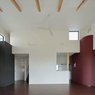 2階LDKは高窓からも採光し、広範囲に光を届けている。仕切り壁の向こうはキッチン。写真左は奥さまの書斎に続くブルーの壁。右はご主人の希望を取り入れた寝室に続く赤い壁。共用空間のLDKでそれぞれのイメージカラーが出会うデザインで、愛着の湧く唯一無二の空間になった