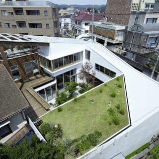 中庭を中心に住空間をスパイラル状に構成。手前がピアノ教室の屋上につくられた屋上庭園、左の茶色の屋根が既存住宅。奥は1階がLDK。デッキテラス奥の木製外壁部分は中2階の浴室と屋上テラス。その右の白壁部分は2階の寝室。道路側は1階がメインエントランス、中2階が書斎