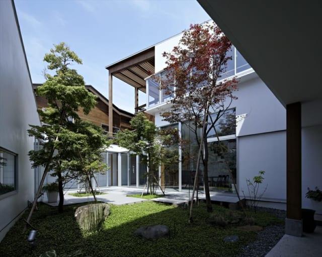 爽やかな青空を望む緑豊かな中庭。1階は写真左から、ピアノホール、ピアノ教室、渡り廊下とつながり、奥のガラス張りの部分がLDK