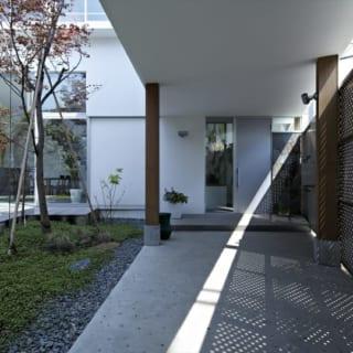 1階メインエントランス。写真右の道路に面した門扉を入ると、中庭の空と緑が迎えてくれる。門扉はパンチングで風通しを良くしてあり、中庭の湿気対策も万全