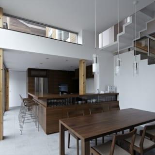 光がたっぷり降りそそぐ1階LDKのダイニング&キッチン。オリジナルのキッチンにはニューギニアウォルナットを使用。奥の階段をのぼると中2階の浴室と、屋上庭園へ続くデッキテラスがある