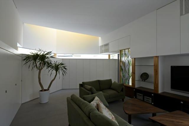 1階LDKには、以前の家にあったステンドグラスを設置。造り付けの壁収納の上部は一部が吹抜けになっており、その上には天窓が。自然光が色みを帯びるよう、天窓近くの壁の色はゴールドにしてある。天からそそぐ光が柔らかなイエローになり、神秘的な雰囲気に