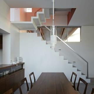 自然光を壁の色で色づける遊び心は階段にも。2階への階段の壁は赤いため、入る光が夕焼けのような色になる