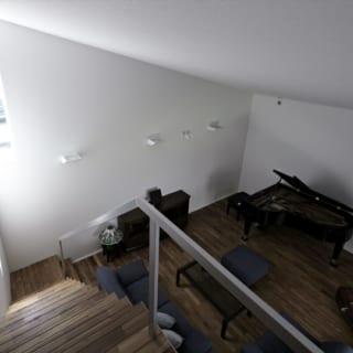 ミニコンサートなどを楽しめる1階ピアノホールは、床にチークフローリングを使用した高級感あふれる空間。手前の階段は中2階の書斎に続く。階段下には専用エントランスがあり、ピアノ教室の生徒さんはホールへ直接入ることができる