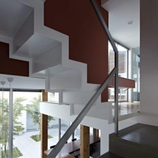 LDK~中2階への階段と、中2階~2階への階段の踊り場。2階への階段は和の趣がある赤で和モダンな印象
