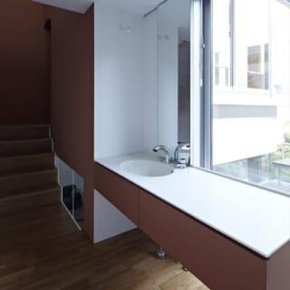 中2階の洗面室。鏡以外の正面は屋上庭園や中庭の緑を望む大きな窓。気持ちよく身支度ができる