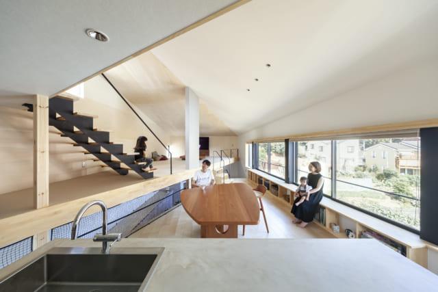 2階キッチンからダイニング、リビングを見る。2階は四角い空間を斜めに区切って床の高さを変え、ダイニング、リビングを使い分けられるようになっている。ダイニングは眺めのよい東側が長辺となる三角形で眺望は抜群。窓際の造作棚はベンチとしても大活躍