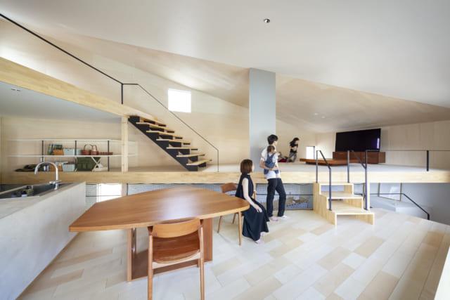 ダイニングの窓際からリビングを見る。ダイニングとリビングの間に仕切り壁や建具はなく、天井はひと続き。斜めに区切ったおかげでどちらも幅広のスペースがあり、落ち着いて過ごせる。リビングの床下のアキから見えるのは1階の玄関ホール。黒い階段の上にはロフトもある