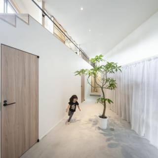 1階の大きな玄関ホール。白いカーテンを開けると壁一面の造作棚。大容量で家中の収納を担える。ここは2階リビングの真下になり、2階同様三角形。床はコンクリート敷きでアパレルショップのような洒落た雰囲気。写真左の壁向こうは、奥から洗面&浴室、寝室、トイレが並ぶ