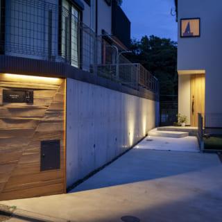 敷地は旗竿地なので道路から玄関までのアプローチも長く、隠れ家的な佇まいに。木製の表札は長方形を斜めに区切ったデザインで、「斜めの空間」というK邸の個性を表している