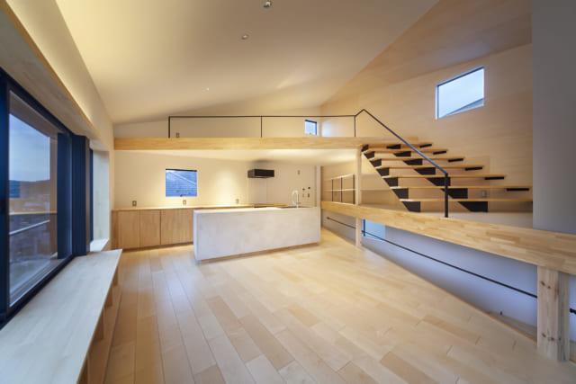 2階への階段をのぼりきったところからLDKを見る。ダイニングへの入口は三角形の鋭角に当たるため、奥のキッチンに向かって空間が広がる形になり、実際の床面積以上に広く感じる効果がある