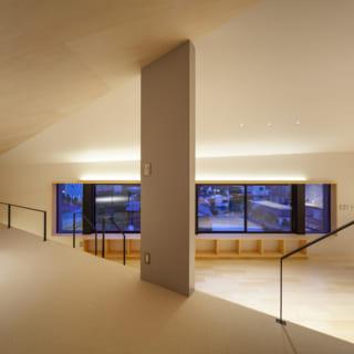 リビングは床が数段高いため、その分天井が低くなり「こもり感のある床座のリビング」を可能にした。リビング・ダイニングはひと続きだが、床の高さや天井の素材が異なることで、本能的に「違うスペース」と感じられる。グレーの小さな壁もリビングのほどよい独立感を創出
