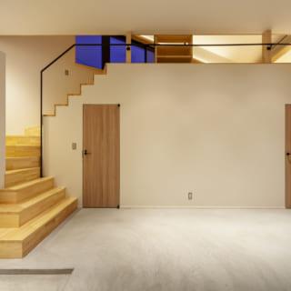 1階玄関ホールの階段まわり。左の扉がトイレで、右の扉が寝室。さらに右に行くと洗面&浴室がある。上部のアキから2階ダイニングが少し見えて視線が抜け、一体感と開放感が生まれている