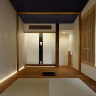 2階の和室。写真奥の床の間に飾っているのはお気に入りの文庫本。床の間の右手は一見すると白壁だが隠し扉になっており、開けると浴室がある。写真右は縦格子の引き戸。この引き戸は1階の吹抜けに面し、開け放すと階下のカウンターを見下ろせる