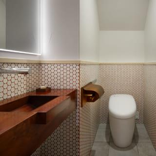 トイレには、施主の田中さんがつくった木製の手洗いが。漆塗りのペーパーホルダーも田中さんの手によるもの