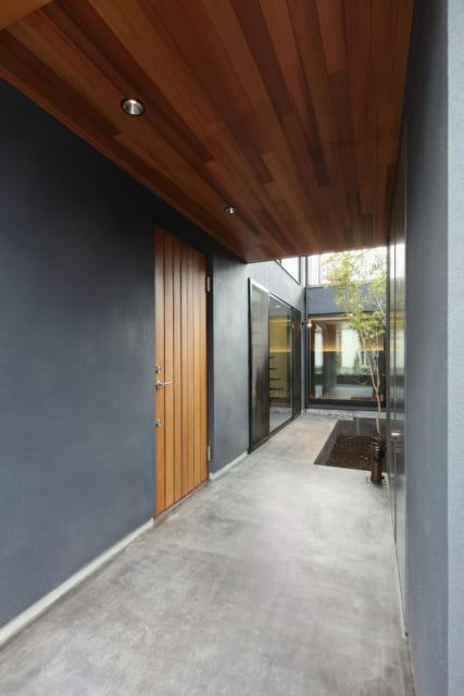 屋根付きの玄関ポーチ。ポーチ床はコンクリートに着色したシンプルな仕上げ。視線の先には中庭が広がる