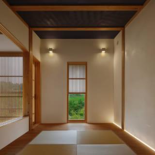 和室から道路側の窓を見る。縦長の窓は、前庭の緑を切り取るピクチャーウインドー。すがすがしい木の葉の日本画を飾っているかのよう