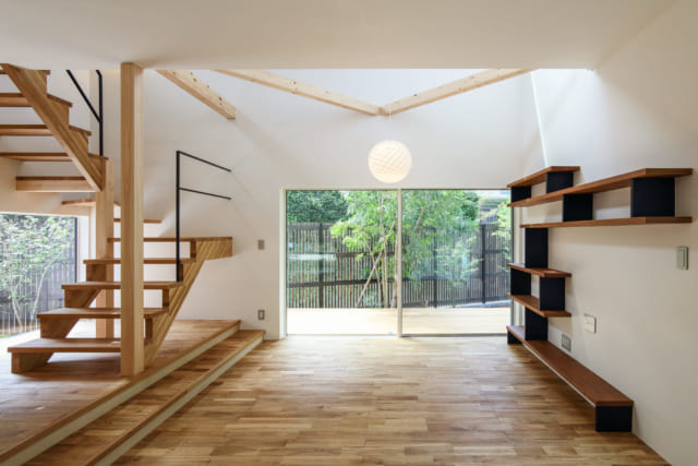 リビングから道路側を見たところ。リビングはダイニングより少し床を下げ、天井の高い空間とした。軽やかにデザインされたリビング内階段のまわりは吹抜けになっており、上部の窓から明るい自然光が降りそそぐ。写真右の造作棚もデザイン性が高く、空間を彩るオブジェのよう