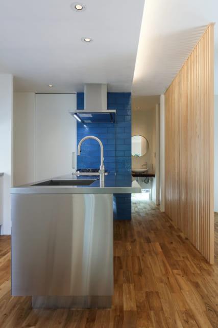 オールステンレスのスタイリッシュなキッチン。壁の一部に用いられたコバルトブルーのタイルが高級感を演出