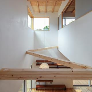 階段まわりの吹抜け。天井はあらわしにして高さを出した。耐震の構造材もデザインされ、インテリアの一部に