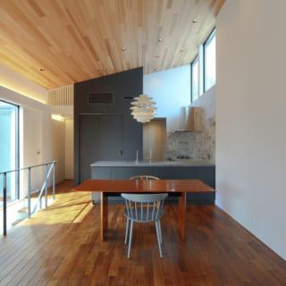勾配天井がおおらかな開放感を生み出す2階LDK。写真左は中庭に面した大開口。写真奥のキッチンの上部にはハイサイド窓がある。どちらからも燦々と自然光が差し込み、明るく居心地のよい空間となった