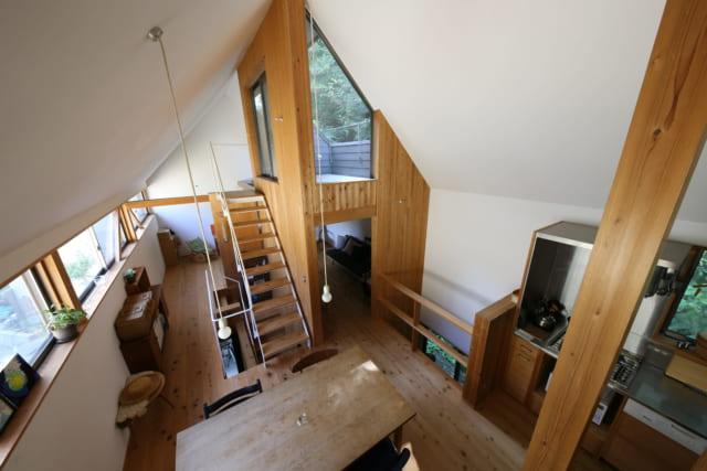 2階。写真左の南面には連続窓。ルーフテラスは室内上部にせり出すようにつくられており、空や山の緑といった自然との距離が近い。階段の吹抜けからは1階の玄関ポーチ、キッチン横の吹抜けからは1階屋外の緑が見え、2階全体が宙に浮いた「空のデッキ」のように感じられる
