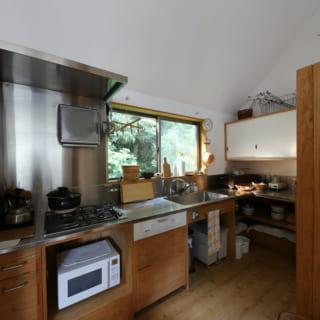 ゆったりとしたキッチンは、スギ材とステンレスでつくったオリジナル。ここにも窓があり、緑豊かな景色を眺めながら家事ができる