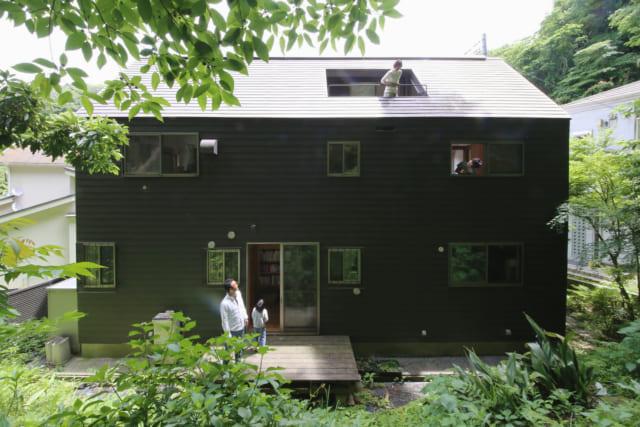 北側の外観。素朴過ぎず、かといって先鋭的過ぎることもない端正でかわいい外観デザインは、緑深い山あいの風景によく映える。屋根に穴が開いているように見える部分は、屋根の斜面を内側に切り取ってつくられたルーフテラス。まさに屋根にいるような感覚を味わえる楽しい空間だ