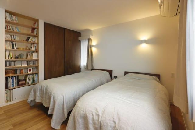 寝室にも収納庫と本棚が。対角線上に2カ所窓を設けて、しっかり通風も確保する。照明はダウンライトと壁付の枕元灯