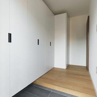 玄関を入って左壁面がすべて収納に。開けると家族の靴がずらりと並ぶ。一番奥の収納庫にはご主人のゴルフ道具が収まる。
