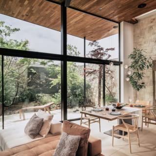 2階LDKのリビング・ダイニングスペース。チークの天井もタイルの床も、同じ素材のままテラスまで大きく張り出し、テラスとLDKが一体化。邸内にいながら太陽光や木々の緑、青空をダイレクトに感じられる空間だ