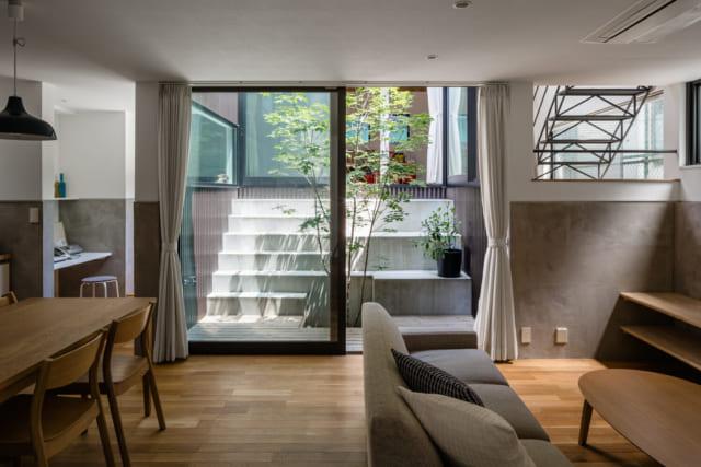 建物は中庭を周遊して2階へ上がる「ロの字型」。写真左に行くとカウンター付きのワークスペースと通路、階段があり、中2階の子ども室に続く。LDKの向かいに位置する子ども室へは、中庭の階段からも行ける。写真右上部には中2階から2階へのぼるアイアンの室内階段が見える